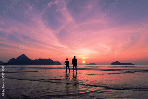 Fond de hotte en verre imprimé Lavende Two lovers standing together on a tropical beach, beautiful sunset in the background