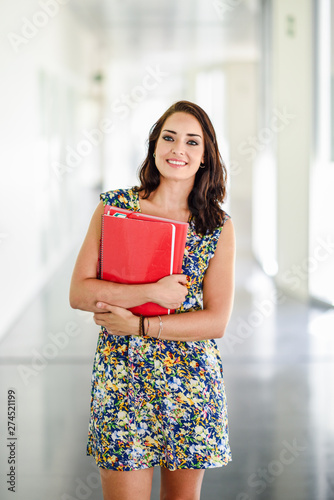 Young adult student woman in a hallway of her school.