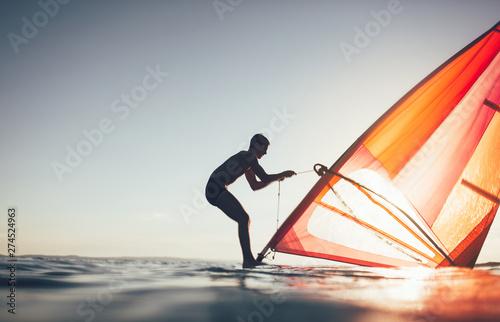 Foto  Silhouette of windsurfer uplift windsurf board sail
