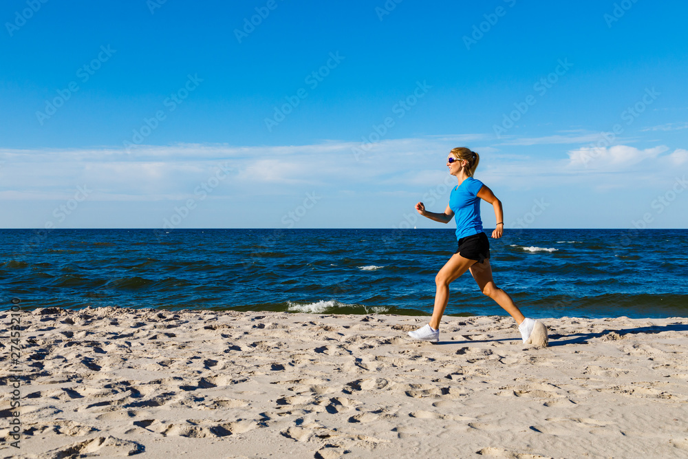 Fototapety, obrazy: Young woman running, jumping on beach
