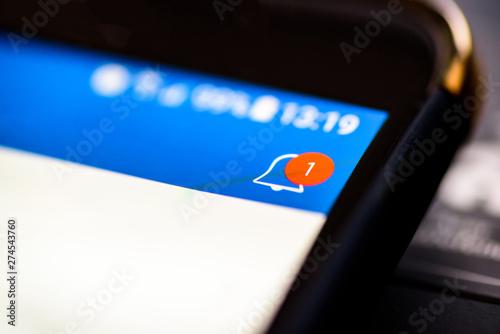 Fotografiet Notification bell button on smartphone app screen closeup