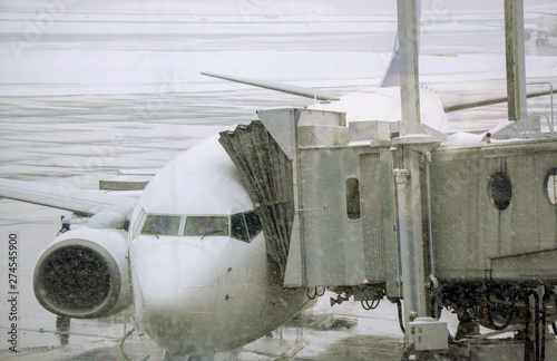 Fototapety, obrazy: Closeup jet bridge and white airplane parked on airport ground and cotton snowing in winter weather.