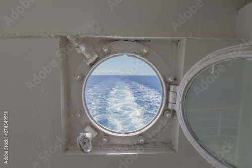 Fotografie, Obraz  metal porthole scuttle on a fast ferry with the view of the backwash and waterwa