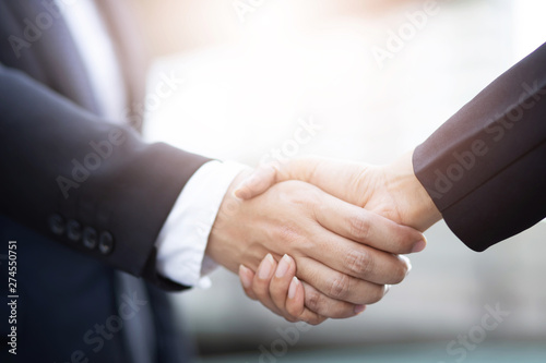 Fotografia  Closeup of a businessman hand shake businesswoman between two colleagues  OK, succeed in business Holding hands