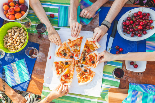 Poster Montagne hands of girlfriends share slices of pizza from a table