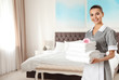 Chambermaid with stack of fresh towels in hotel room. Space for text