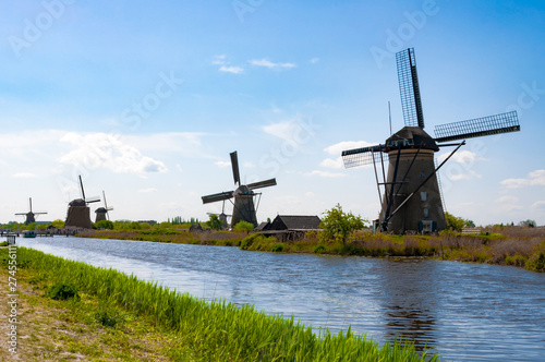 Garden Poster Mills Rural lanscape with windmills close to the river above the blue sky and pretty clouds