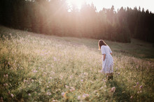 Stylish Girl In Rustic Dress Walking In Wildflowers In Sunny Meadow In Mountains. Boho Woman Relaxing In Countryside Flowers At Sunset, Rural Simple Life. Atmospheric Image. Space Text