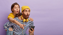 Surprised Male Gives Piggyback To Woman Who Points Finger Into Distance, Hold Smartphone Device, Listen Music From Palylist, Stare With Bugged Eyes, Isolated On Purple Background With Free Space
