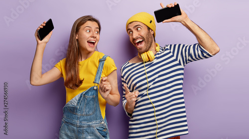 Millennial happy girl and man hold cellphones, dance to music, have fun together, look joyfully at each other, enjoy fantastic sound, listen music using headphones, isolated on purple background - 274566930