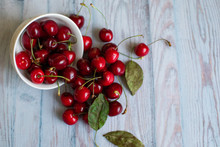 Fresh Red Cherries In A White Plate On A Light Blue Background, Space For Text, Concept Of Natural Fresh Vegetarian Food