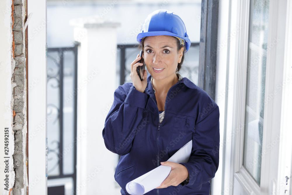 Fototapety, obrazy: female engineer wearing helmet using a smartphone