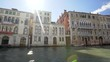A busy canal in Venice showing boats and houses Italy