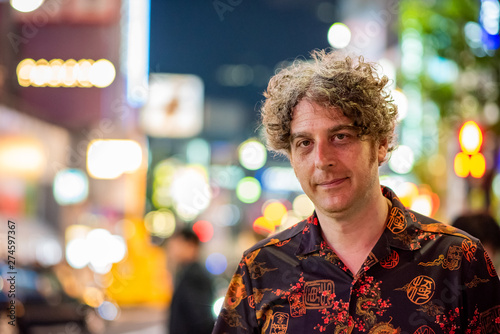 Photographie  Portrait of a middle aged man traveling and enjoying the nightlife in Tokyo, with beautiful blurry lights behind