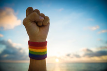 Gay Pride Hand Punching The Air Wearing Rainbow Colors Wristband Against Scenic Beach Horizon
