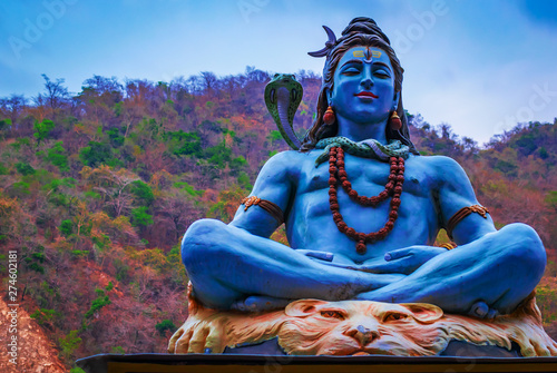 Obraz na plátně Idol of Indian God Shiva, at the bank of river Ganga in Rishikesh with blurred temple in background , the yoga  capital of India