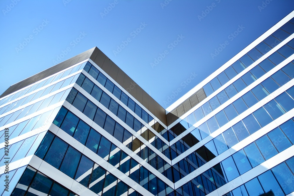 Fototapeta New office building in business center. Wall made of steel and glass with blue sky.