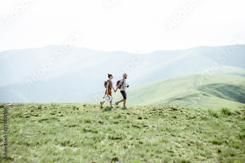 Foto auf Gartenposter Olivgrun Couple walking with backpacks on the green meadow, traveling in the mountains during the summer time, wide landscape view