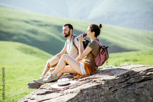 Fototapeta Young couple drinking water while resting on the rock during the travel in the mountains obraz