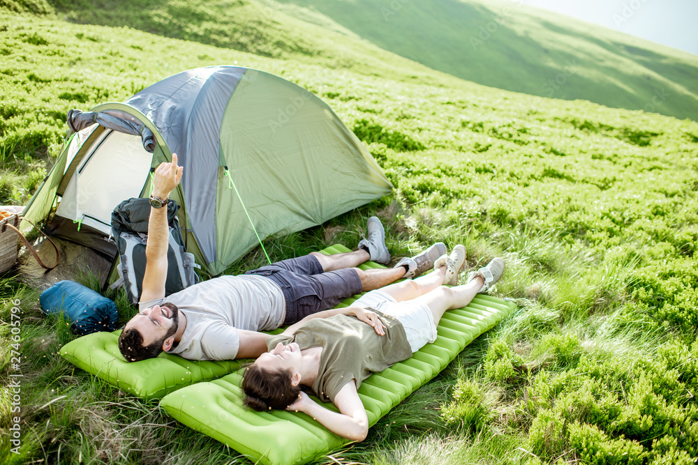 Fototapeta Young and cheerful couple lying on the mattress at the campsite, enjoying summer time while traveling in the mountains