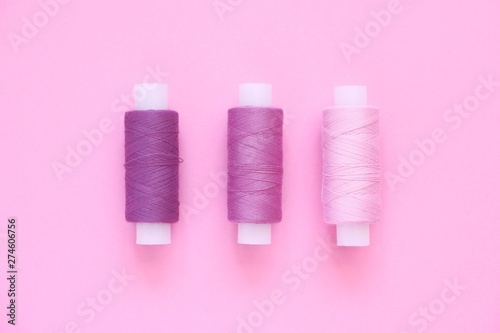 Canvastavla  Sewing thread kit of lilac (pink, violet, crimson) sewing thread on a pink paper backgroun, copy space for text