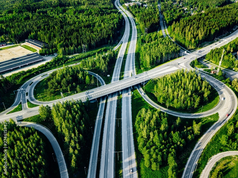 Fototapeta Aerial view of highway and overpass with green woods in Finland.