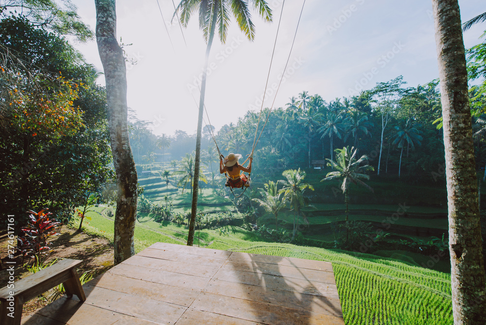 Fototapeta Beautiful girl visiting the Bali rice fields in tegalalang, ubud. Using a swing over the jungle. Concept about people, wanderlust traveling and tourism lifestyle