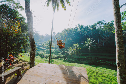 Obraz Beautiful girl visiting the Bali rice fields in tegalalang, ubud. Using a swing over the jungle. Concept about people, wanderlust traveling and tourism lifestyle - fototapety do salonu