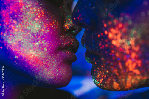 Couple kissing in the disco club with fluorescent paintings on the faces Fototapete