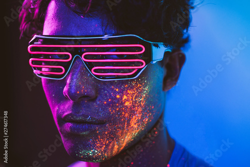 Handsome boy dancing at the rave party with fluorescent paintings on his face Canvas Print