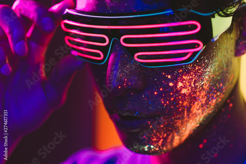 Photographie Handsome boy dancing at the rave party with fluorescent paintings on his face