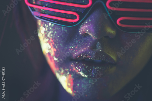 Beautiful young woman dancing and making party with fluorescent painting on her face Фотошпалери