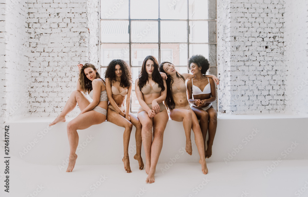 Fototapeta Group of women with different body and ethnicity posing together to show the woman power and strength. Curvy and skinny kind of female body concept