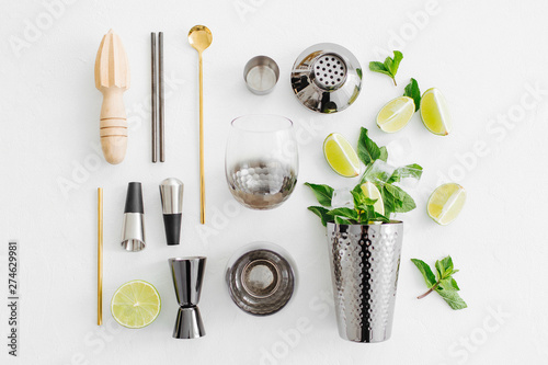 set-of-bar-accessories-for-cocktail-making-shaker-jigger-glass-spoon-and-other-bar-tools-with-lime-and-mint-leaves-on-withe-background