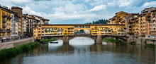 The Ponte Vecchio, Or Old Bridge, Is A Medieval Stone Arched Bridge Over The Arno River In Florence, Italy.  It Is Now A Tourist Destination With Several High End Jewelry Shops.