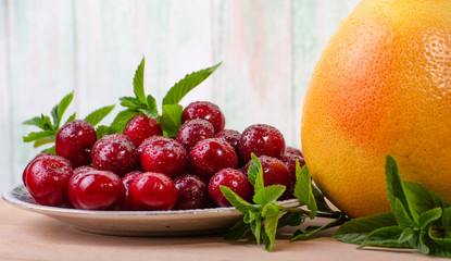 grapefruit on a light background next to a plate of ripe cherries decorated with sprigs of peppermint