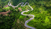 Aerial View Road In Mountains, Road Running Through Green Hills Forest With Car.