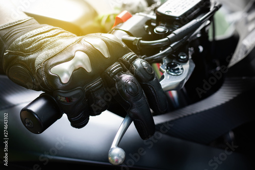 Valokuva  Close up of throttle control hand and brake lever motorcycle, Hands wearing blac