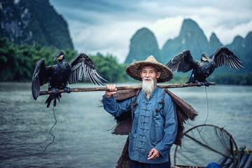 Cormorant fisherman in Traditional showing of his birds on Li river near Xingping, Guangxi province, China.