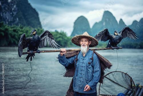 Photo  Cormorant fisherman in Traditional showing of his birds on Li river near Xingping, Guangxi province, China