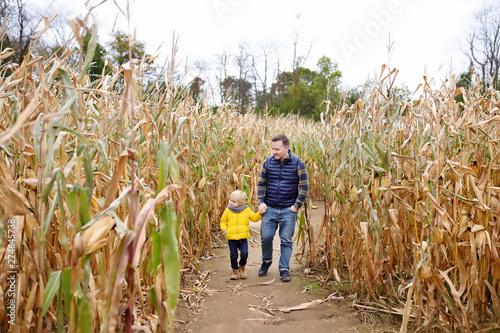 Little boy and his father having fun on pumpkin fair at autumn Fototapeta