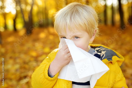 Little boy sneezing and wipes nose with napkin during walking in autumn park Tablou Canvas