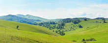 Beautiful Hilly Panoramic Landscape With Green Grassy Hills In A Sunny Summer Day