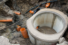 Building Concrete Sewage Tank, Flowing Water Trough Orange Pipes  In The City.