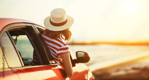 Fototapeta happy woman girl goes to summer travel trip in   car. obraz