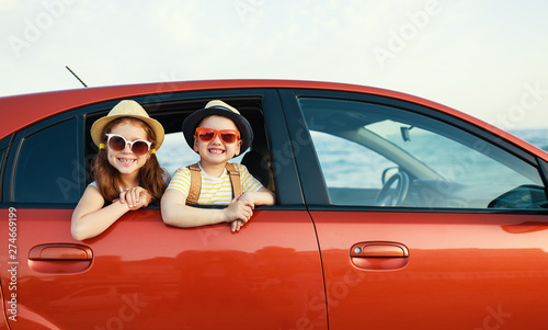 Fotomural happy children girl and boy goes to summer travel trip in car.