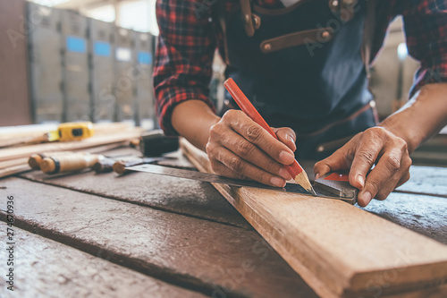Carpenter working with equipment on wooden table in carpentry shop Fototapeta
