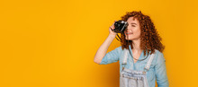 Take A Good Shoot. Positive Curly Haired Teenage Girl Make A Photo On Yellow Background.
