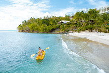 Men In Yellow Kayak In The Ocean By The Beach Of The Tropical Island Of Saint Lucia Caribbean, Man Kayakking