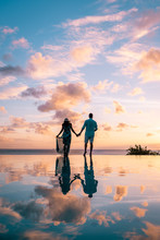 Couple Walking On The Beach Du...